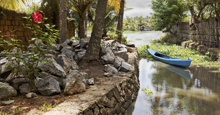 landscape of Kerala backwaters India artery berthed blue canoe local stone granite boulders hybiscus bush with solitory bloom, toe path horizontal with crop space