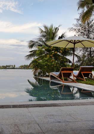 crop margin: pescador de la ma�ana, tumbonas, la eternidad junto a la piscina Laguna Verde Kerala India, el cielo azul, nubes, verticales, con copia espacio y el margen de cultivos Foto de archivo