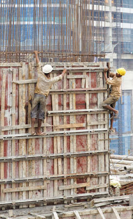 Editorial vertical portrait of men at work on a 18 storey construction site wearing slippers flip flops disregarding personal safety of protective clothing footwear safety harness whilst making a box for concreteing crop margin copy sapce