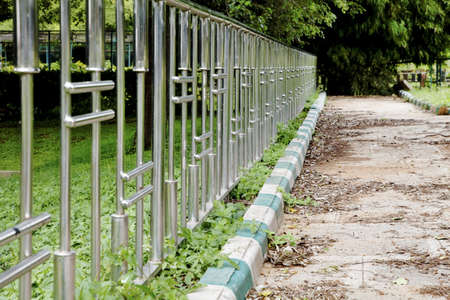 crop margins: landscape horizontal chrome patterned fence and unswept bordered path lush greenery at Botanical Gardens Bangalore India patterns shapes crop margins copy area empty space Stock Photo