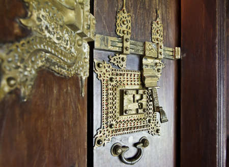 portrait craftsmanship of ornate brass door furniture and detailing in Kerala India