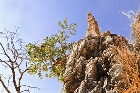 Horizontal landscape of rock formation and man made rock structure, some made made with trees framing a Hindu spritual ribbon tied high up a cliff on a bush. The path is a holy pilgrimage for Hiduism, crop margins and negative spaces Stock Photo - 11696219