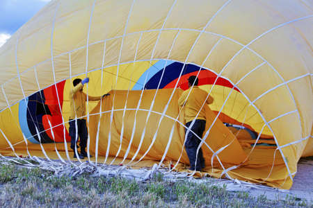 crop margins: Roadies inside a yellow hot air balloon making ready for a flight in Cappadocia Turkey, horizontal landscape with crop margins anfd free space Stock Photo