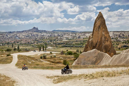 Landscape of dirt riding in Cappadocia on the outsirts of Goreme with Uchisar on the hill backdrop, horizontal, crop margins with negative space