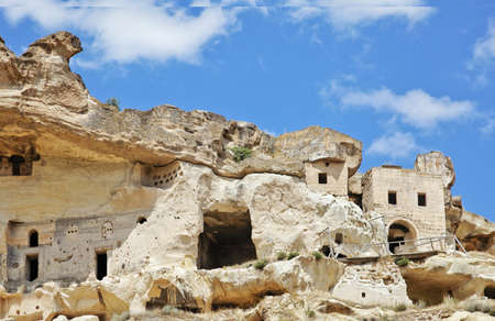 Landscape on outskirts of Goeme, Cappadocia, of anceint township built into limestone caves showing exterior architecture, blue cloudy sky with negative area and crop margins