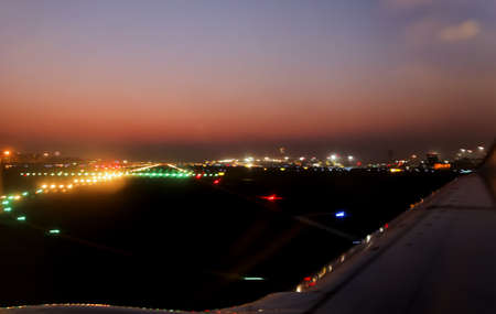 Horizon landscape of night time runway lights at Mumbai International Airport during take off, crop margins, copy space and empty areas photo