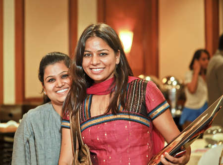 Two smiling Indian pretty hostesses at an event with clip board and mobile cell phone ushering guests, crop margin and empty copy space photo