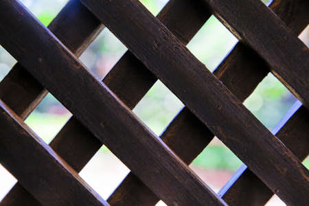 criss: landscape of dark man made wooden lattice screen of garden greenery, lawns and drive Stock Photo