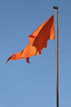flying monkey: saffron flag swaying in the breeze at Hanuman Hindu Temple Mahabhaleshwar India on clear blue sky