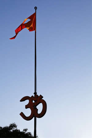 Sillhouette of trees and Hindu Om sign, flag pole and saffron flag fly in the breeze photo