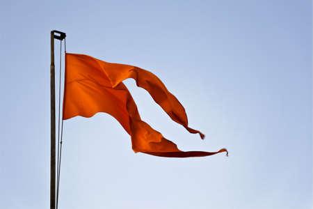 Rusty flag pole with saffron coloured flag a symbolic emblem of a Hindu Temple