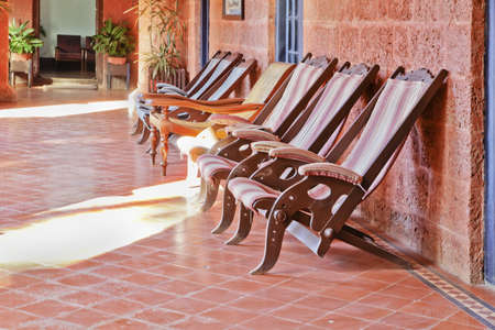 crop margin: Landscape of dexk chair loungers on a quarry tiled floor with red brick walls early 20th century styling Stock Photo