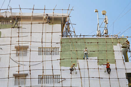 Mumbai, India, editorial, wooden scaffolding erected against high rise wall with team of decorators painting supported by harnesses