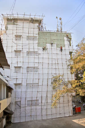 Mumbai, India, editorial, wooden scaffolding erected against high rise wall of industrial office blockwith team of decorators painting supported by harnesses