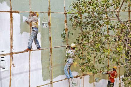 Mumbai Indian horizontal of exterior bare foot decorators wooden scaffold India painting a building wall