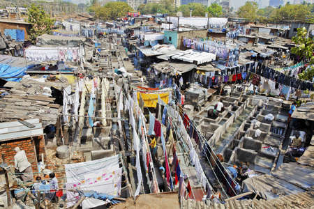 Mumbai, Dhobhi ghat, assembly line of wash tubs and bays with washed laundry out to dry on washing lines