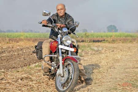 crop margin: Gujarat, India, Senior sin afeitar citizin indio var�n en un crucero de color rojo dos ruedas de motocicleta