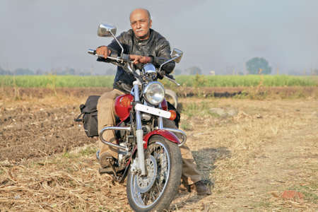 Gujarat India, Senior unshaven Indian male citizin on a red cruiser two wheeler  motorcycle photo