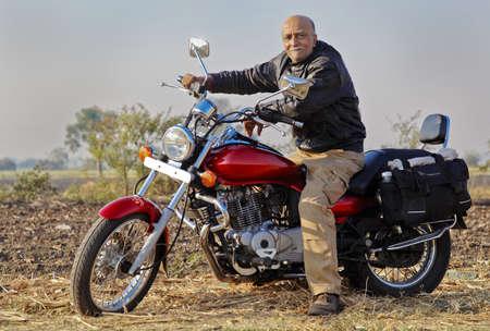 crop margin: Gujarat, India, en un var�n ciudadano de tierras de labrant�o rurales alto en su motocicleta Cruiser de color rojo