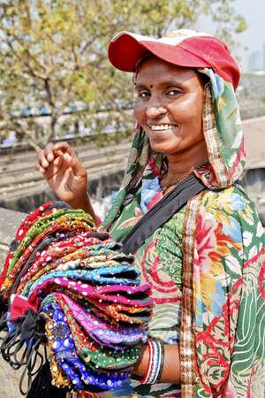 tourist spot: Mumbai tourist spot, Dhobhi Ghat, protrait of colorful smiling purse street vendor with baseball hat