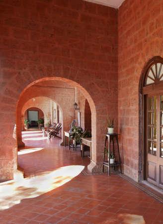crop margin: Veranillo de San Mart�n bajo los arcos sobre un suelo de baldosas de cantera con el estilo art deco y el detalle de hamacas, tumbonas y artefactos Editorial