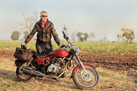 negative area: Gujarat, India, middle aged caucasian with red indian motorbike in a rural setting of seedings growing on a sugar cane farm Stock Photo