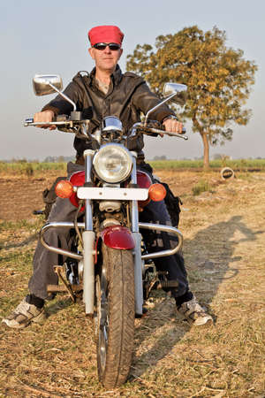 negative area: portrait of an european biker with headgear in the farmlands and hinterlands of Gujarat, India Stock Photo