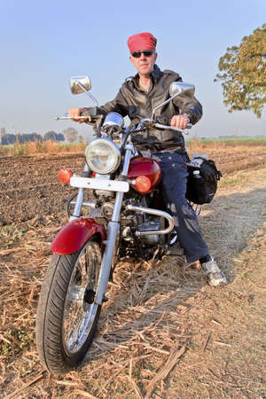 Gujarat, India full length portrait of european biker in hinterlands of rural famland on an Indian made red cruiser photo