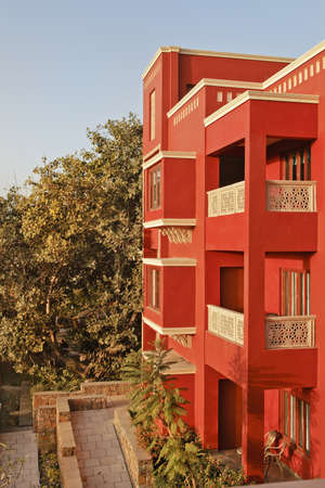 crop margin: Portrait of generic modern architeture of 3 storey concrete block, brightly colored, blue sky and garden layout