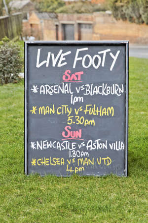 crop margin: Lancashire, England, UK - February 2, 2012  Editorial, Bar sign outside a UK public house showing live soccer matches itinery to drum up business from footy fans