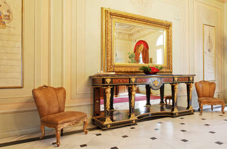 crop margins: Bosphorus Palace Hallway, Istanbul, Turkey - July 2, 2011  Elegant Ottoman style of furniture and interior decorations with paneled walls, visitors chairs, large mirror, side table and tiled flooring