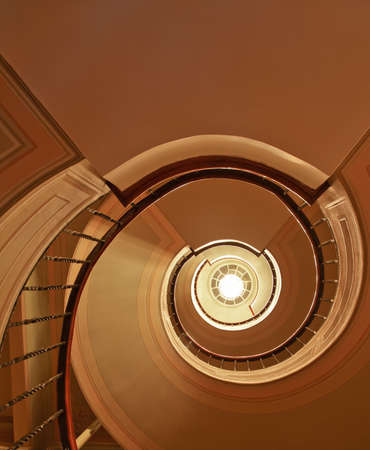 Architectural detail and interior design of spiral staircase, stairwell and daylight from skylight