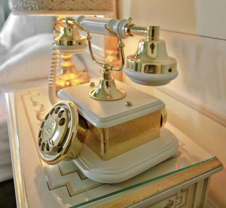 'bedside table': Interior room design with ornate ceramic dog and bone style retro telephone on bedside table with lamp
