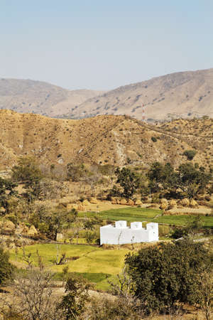 crop margin: Vertical of farmland patterns of rural Rajasthan near Kumbhalgarth India with whit farm house, distant hills and blue sky Stock Photo