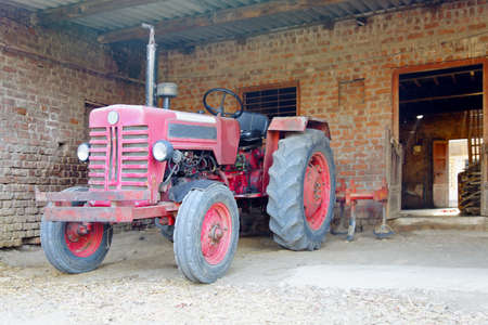crop margins: Landscape of Indian tractor parked in a stable with ploughing attachment Stock Photo