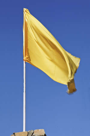 Vertical portrait of silky yellow flag aginst a deep blue sky Stock Photo