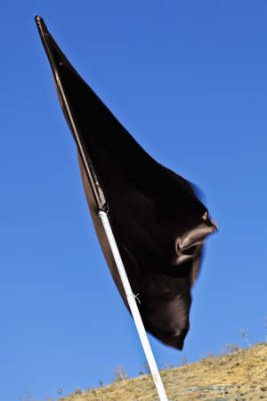 Diagonal shot, portrait, vertical of a plain silky black flag waving in a gentle breeze