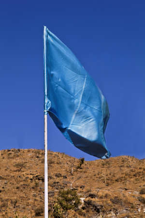 Portrait of a vertical flagpole with a silky blue turquoise flag waving in the breeze