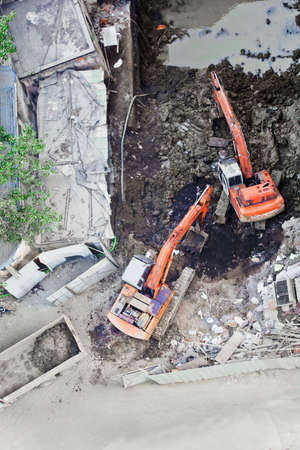 Construction site in Mumbai, India, two diigers working together to move soil onto a tipper truck, aerial view Stock Photo