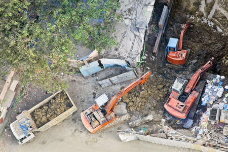 Any orientation aerial of construction site in Mumbai India where 3 diggers are moving earth onto a tipper Stock Photo - 13302035