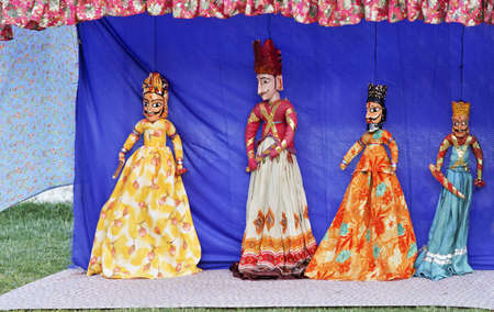 crop margins: Rajasthan tribal puppet show by local tribal performers using hand crafted vividly colorful string dolls to portray historical characters, copy pace and crop margins