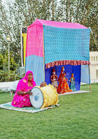 drumming: Portrait of an early evening outdoor performance on a lawn by traveling troupe man and wife team of Rajasthani puppetiers in India Stock Photo