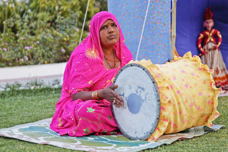 crop margin: Indian lady performer of folk lore stories as part of a husband and wife team in Rajasthan India Editorial