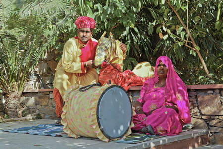 Landscape portrait of a Colorful couple travelling puppetier musician resting in the shade before a performance