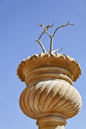 negative area: Portrait of Upward view point of indigenous Rajasthan stone carved and crafted plant pot with stick plant on a clear blue cloudless sky