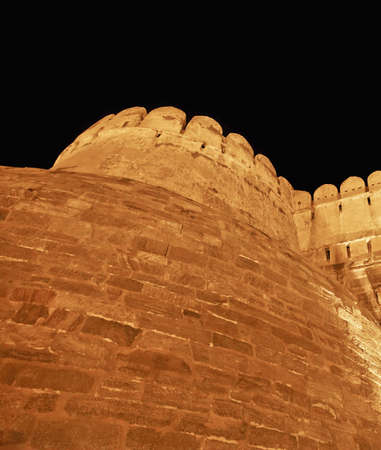 tourist spot: Street lights light up the fortification and bastions of Kumbhalghar Fort, India and night time Editorial