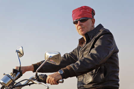 red bandana: Side on take of whtie motorbiker posing with sun glasses and red bandana