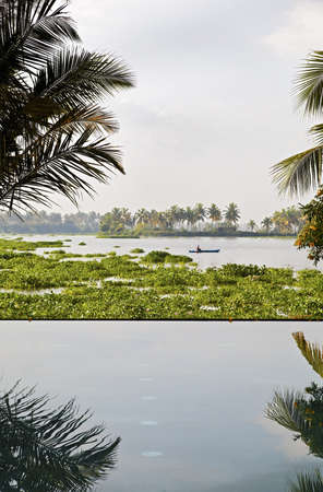 Vertical shot of infinity pool over a lake of hyacinth with mature gardens and a lone fisherman in the distance