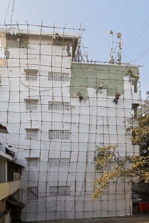 Gang of Indian barefoot Decorators painting exterior of a five story industrial building on a bamboo scaffold