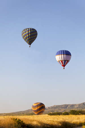 Colourful hot air balloons rising over the ridge  A generic portrait was taken early morning in Cappadocia, Turkey  Stock Photo - 14760611